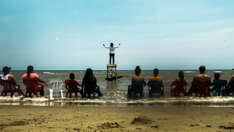 Un grupo de personas contempla desde la orilla de la playa a un hombre sobre una plataforma dentro del mar dirigiendo un concierto del mar